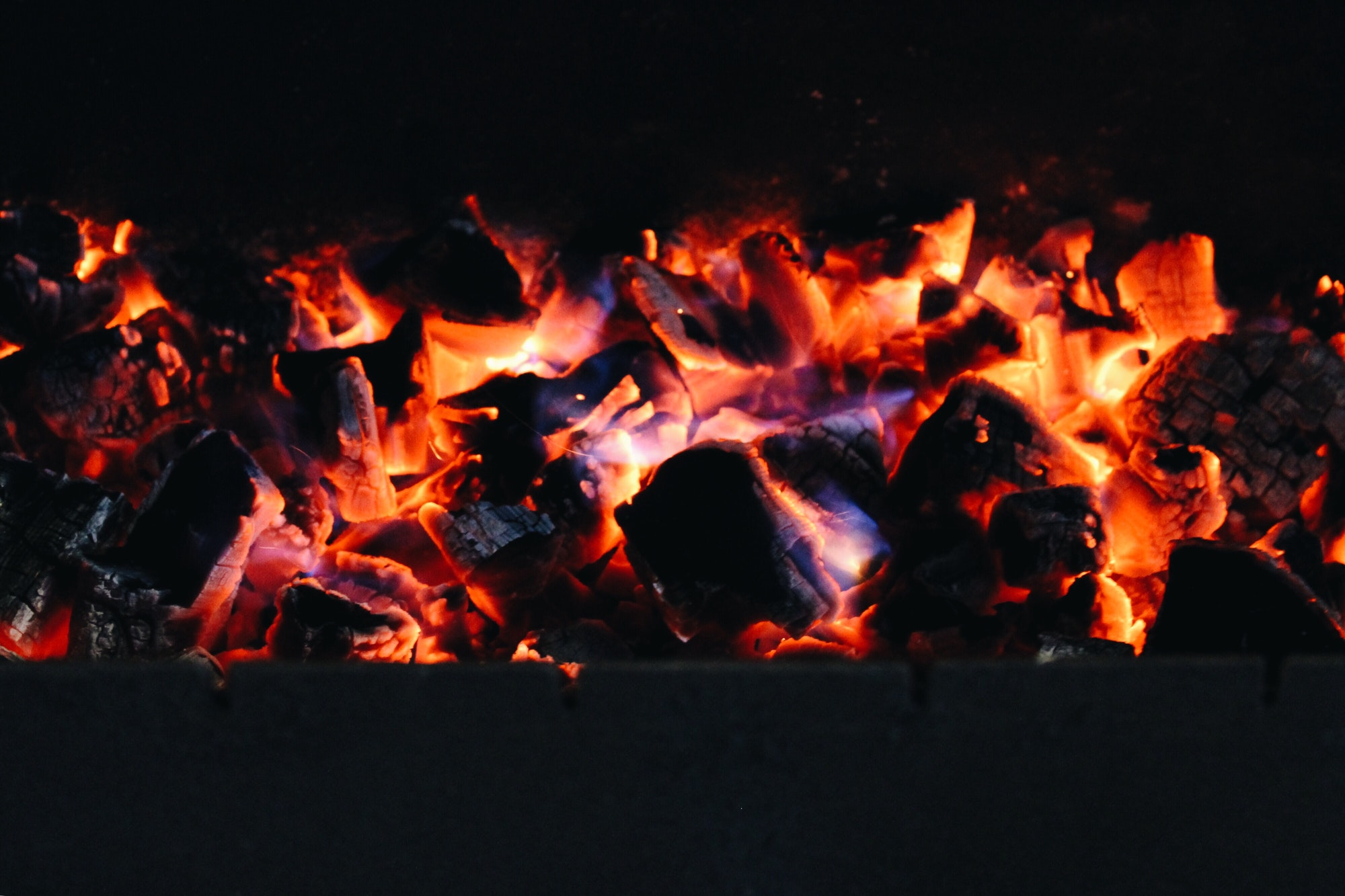 The burning coals in a brazier for meat